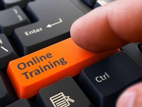 Finger Presses Orange Button Online Training on Black Keyboard Background. Closeup View. Selective Focus.
